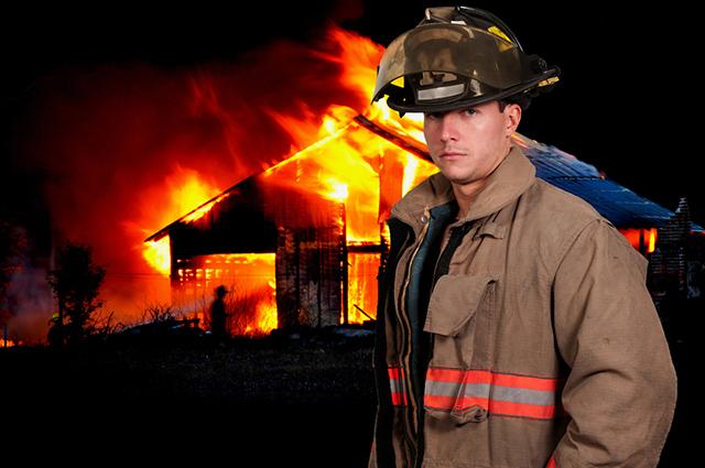 Bombeiro em frente a casa em chamas