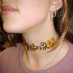 Tatuagem de flor no pescoço