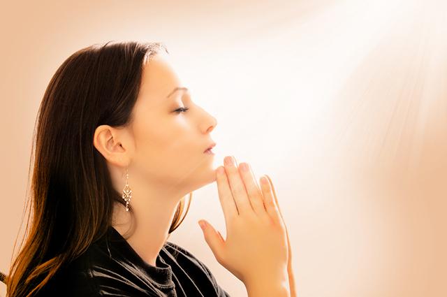 Mulher rezando de mãos juntas e olhos fechados