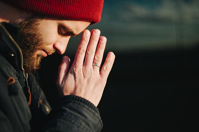 Homem de cabeça baixa e mão unidas rezando