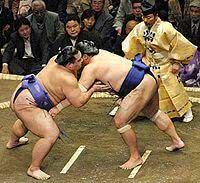 Lutador de sumô aplicando golpe