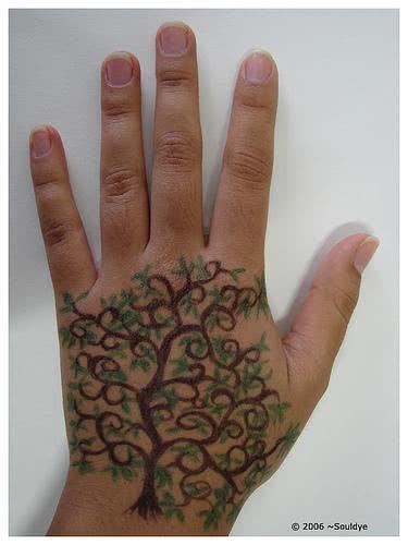 Mão tatuada com galhos de árvore